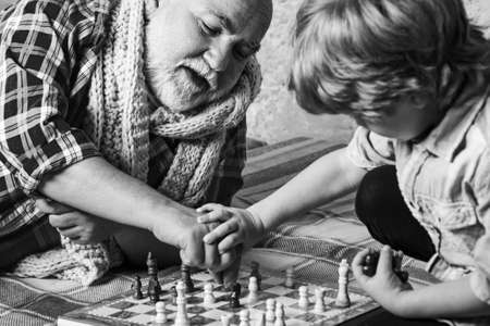 Handsome grandpa and grandson are playing chess while spending time together at home. Chess hobbies - granddad with grandson on a playing chess.