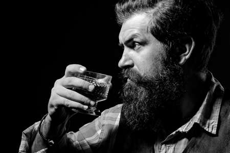 An elegant man suffering from alcoholism drinking whisky. Bearded handsome man holding glass of whiskey. Attractive man in whiskey bar. Imagens