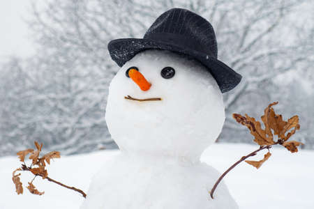 Snowman with light star in Christmas day. Snow man in winter hat. Funny snowmen. Making snowman and winter fun. Snowman gentleman in winter hat.
