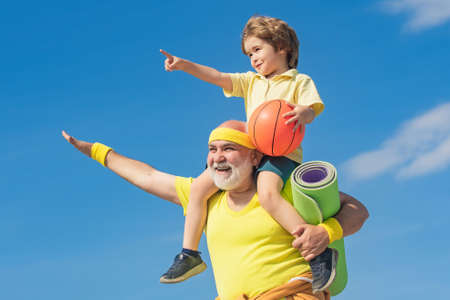 Senior man and child in family health club. Doing sports is free. Grandpa and grandson spotting. Grandfather and child is doing sport outdoors.