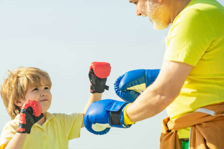 Handsome elderly man practicing boxing kicks. Elderly man hitting punching bag. Grandfather and child fighting poses. Senior trainer and little boy wearing boxing gloves.