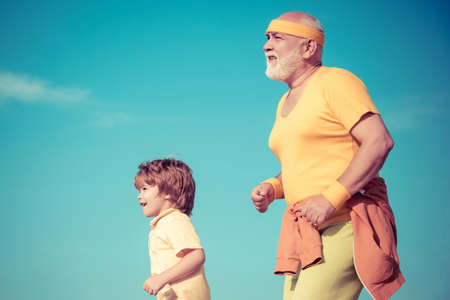Grandpa and child sportsmen jogging outdoors and enjoying sunny day. Like sports. Funny sporty old sportsman and cute little child boy finished his work out.