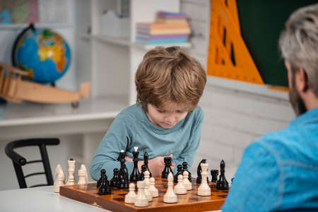 Happy child and childhood. Kid Playing Chess. Intelligent, smart kids. Games good for brain intelligence concept.