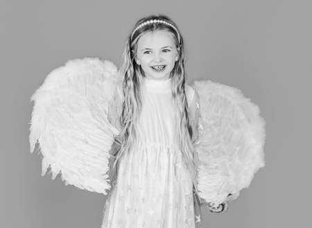 Beautiful young girl wearing angel wings. Child wearing long white dress and angel wings. Cute toddler girl in white wings as Cupid.