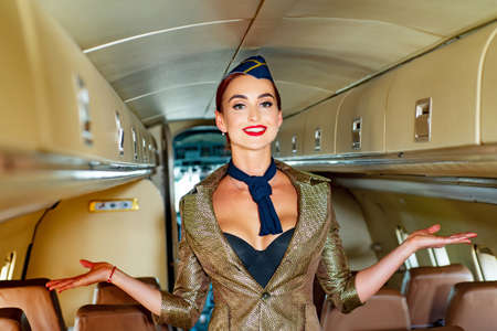Young woman in flight attendant clothes. Happy smiling woman stewardess in uniform waiting for her flight. Stewardess and travel time. Woman and commercial plane.