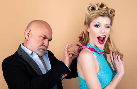 Blonde woman eye wink at camera. Happy blonde woman with luxury hairstyle and makeup smile while her sugar daddy wears a decoration on her neck. Rich elder man with grey hair.