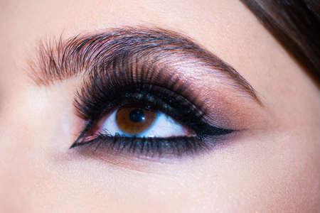 Eyes with make up close up. Makeup closeup. Eyebrow long eyelashes. Beauty salon. Beautiful macro female eye with long eyelashes and smoky makeup. Perfect eyebrows. Cosmetics and fashion visage.