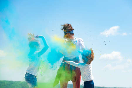 Kids playing with colored splash powder and color dust.