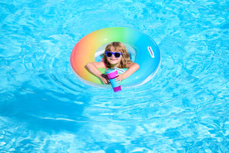 Child in swimming pool. Summer kids cocktail party. Summer beach fun.