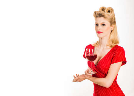 Beautiful woman with glass red wine. Portrait of pinup, dreamy, charming, curly blonde woman tasting old expensive red wine from big wineglass in hand isolated on white background.