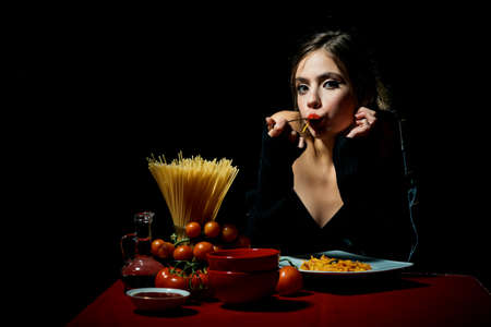 Hungry beautiful woman eat on noodles spaghetti on black background.