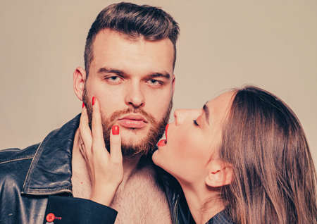Touch his bristle. Girlfriend passionate red lips and man leather jacket. She adores male beard. Passionate hug. Passionate couple in love. Man brutal well groomed macho and attractive girl cuddling