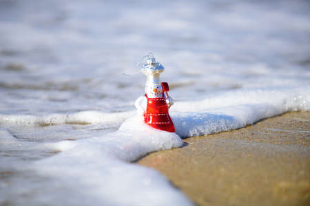 Christmas holiday. Toy snowman on the summer sea. New Year concept.