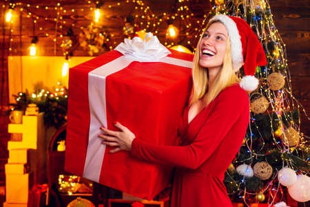 Woman with Christmas mood. Young woman in elegant red dress over Christmas interior background. Luxury Christmas woman. Christmas and new year holidays.