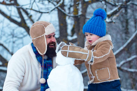 Father and son making snowman in the snow. Handmade funny snowman. Christmas holidays and winter new year with father and son. Happy family plaing with a snowman on a snowy winter walk.