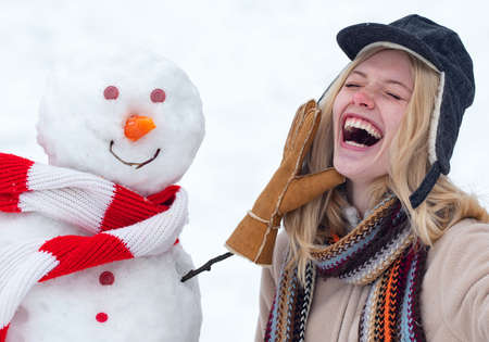 Winter love concept. Happy girl plaing with a snowman on a snowy winter walk. Making snowman and winter fun. Crazy comical face.