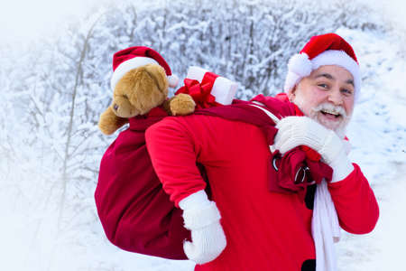 Portrait of Santa in the winter field. Santa Claus on Christmas Eve is carrying presents to children in a bag.