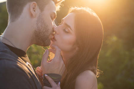 Man with woman kisses. Close up portrait of a beautiful young couple waiting to kiss against sunset light.