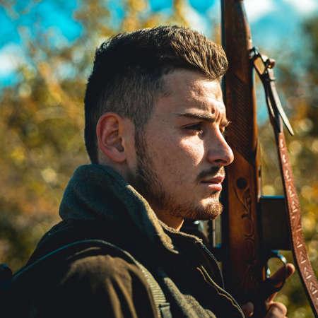 Hunter with shotgun gun on hunt. Hunter in the fall hunting season. Man holding shotgun. Deer hunt. Close up Portrait of hamdsome Hunter.