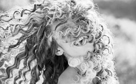 Blonde spring girl with curly beautiful hair smiling. Beauty hair Salon. Fashion haircut. Beauty girl with long and shiny curly hair. Trendy haircuts. Long healthy hair. Spring emotions.