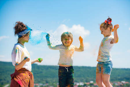 Bright and happy children playing with colored powder.