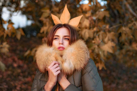 Beautiful exquisite girl standing in the park freezing in a jacket with fur. Autumn queen. Fall season outfit. Modern fashion outfit. Autumn season. Gorgeous pretty woman in furry coat fallen leaf on head as crown. Trendy outfit. Her confidence is stunning
