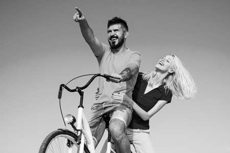 Young hippie couple on sky blue background. Beautiful smiling girl and bearded hipster man is riding the bicycle in the park. Summer vacation. Stylish and loving couple enjoying.