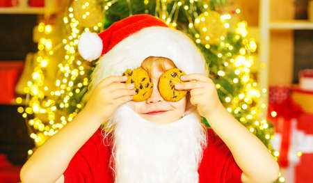 Santa - funny child picking cookie. Santa boy child eating cookies and drinking milk. Santa Claus holding Christmas cookies and milk against Christmas tree background.