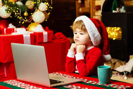Little boy santa hat and costume. Boy child with laptop near christmas tree. Buy christmas gifts online. Christmas shopping concept. Gifts service. Santa little helper. Smart toddler surfing internet