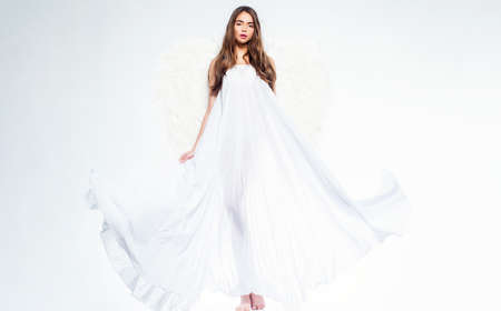 Valentines day and costumes concept. Young woman in angel costume. Angel with gift. Fallen white angel. Beautiful woman posing with angel wings.