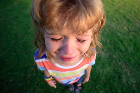 Kids face crying tears. Upset child. Violence in family over children. Concept of bullying, depressive stress or frustration. Top wide view. Stock Photo