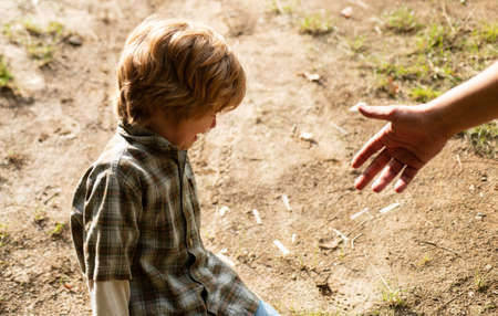 Father giving son a helping hand, hope and support children. A crying toddler sit down on the road. Kids with tears emotional. Upset child. Violence in family over children.