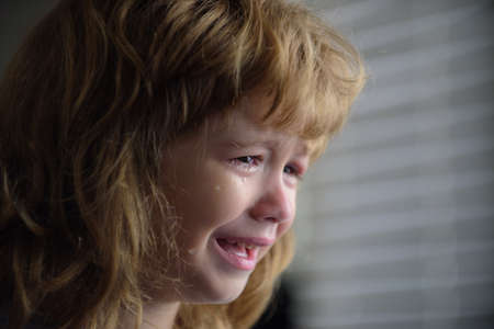 Close up face of little boy crying with tears. Portrait of a kid Cry at home. Child sad Emotions.