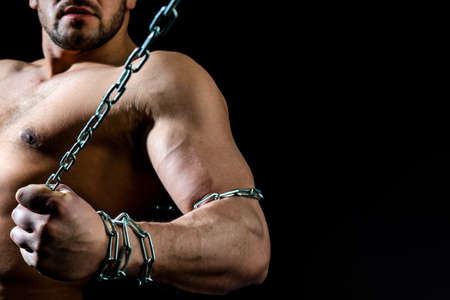 Naked torso man with chain on hand. Broken Chain. Freedom Concept . Brutal man bodybuilder athlete holding a chain on a black background. Stok Fotoğraf