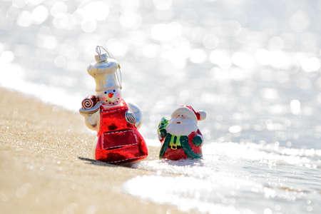 Summer Santa and snowman on the sea.