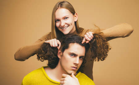Young couple doing a joke over the isolated khaki background. A blonde girlfriend making funny hairstyle to her boyfriend with curly hair.