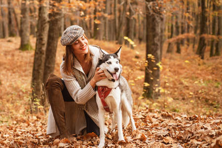 Good looking stylish girl is playing with her husky dog in the autumn forest. Fall is the best time of the year to have a walk with your pet. Autumnal nature and walk with pet concept. Foto de archivo