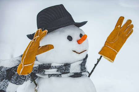 Snowman with light star in Christmas day. Snowman in a scarf and hat. Merry Christmas and Happy Holidays. Cute little snowman outdoor