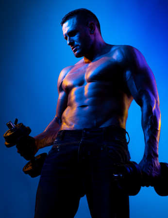 Muscular bodybuilder guy doing exercises with dumbbells isolated on blue neon. Naked athlete with strong body. Shirtless hunk with perfect abs.