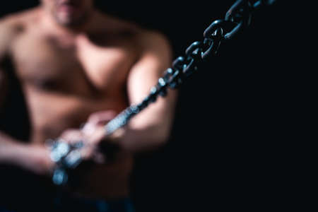 Muscular man with chain. Live life. Concept symbol of freedom. Strong man. Problem solving.