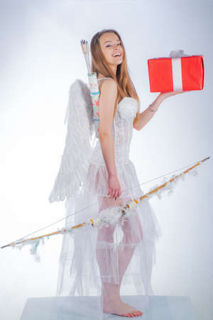 Concept of innocent girl. Love card. Postcard for Valentines Day - copy space. Valentines day. Cupid cute girl with a bow and red gift box.