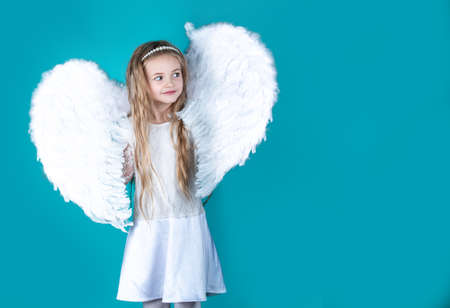 Saint Valentines Day card. Child wearing long white dress and angel wings. Happy angel girl over white. Beautiful young girl wearing angel wings.