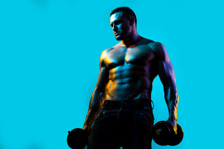 Exercise for the muscles biceps. Muscular bodybuilder guy doing exercises with dumbbells isolated on blue neon.