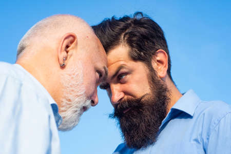Men generations: grandfather and father together. Elderly Senior man and bearded son - two generation concept. Father and son looking at each other.