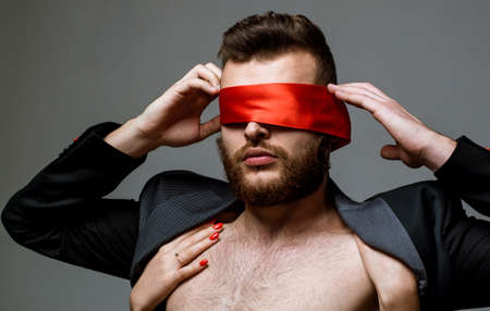 Blindfolded. Woman covering man eyes. Sexy girl closes eyes of a man.