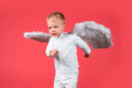 Funny Valentines day. Cupid angel child with wings is fun, isolated on red.