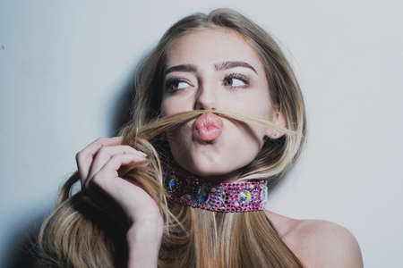 Young playful girl making moustache with her hair. Flirting dating, romantic woman and seduction girl. Beauty girl, beautiful blonde women hair.