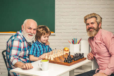 Father teaching son play Chess. Grandfather educated Grandson. Grandfather and grandson concept. Reklamní fotografie