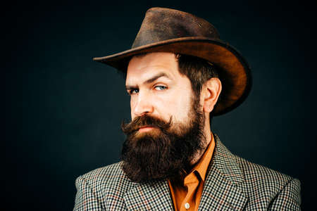 Retro handsome man, portrait face of serious bearded hipster on black background.