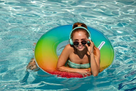 Summer girl in swimming pool. Cute funny teen relaxing with toy ring floating in a swimming pool having fun during summer vacation in a tropical resort. Reklamní fotografie